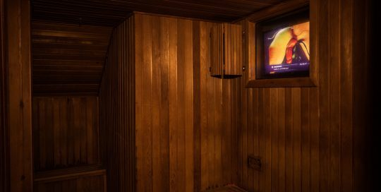 In the back of the dry sauna is a dark room. This dry sauna also features a TV playing the hottest movies.